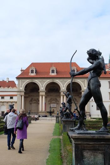 Statue in front of building against sky