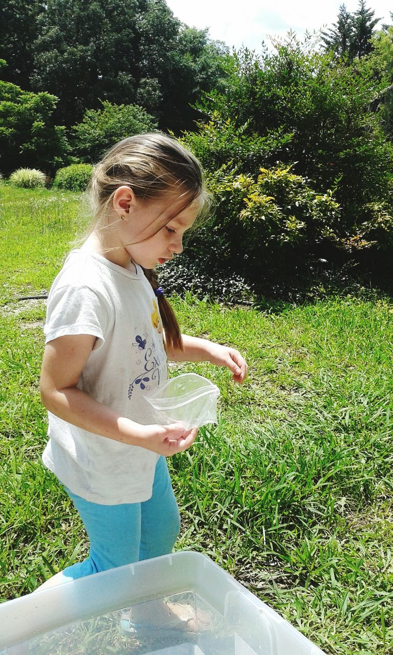 Side View Of Girl Holding Plastic On Grass In Park