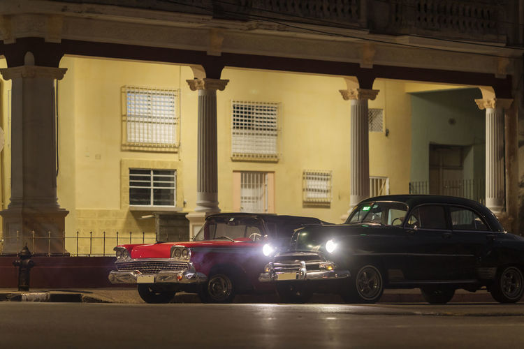 Cars parked on street against illuminated buildings at night