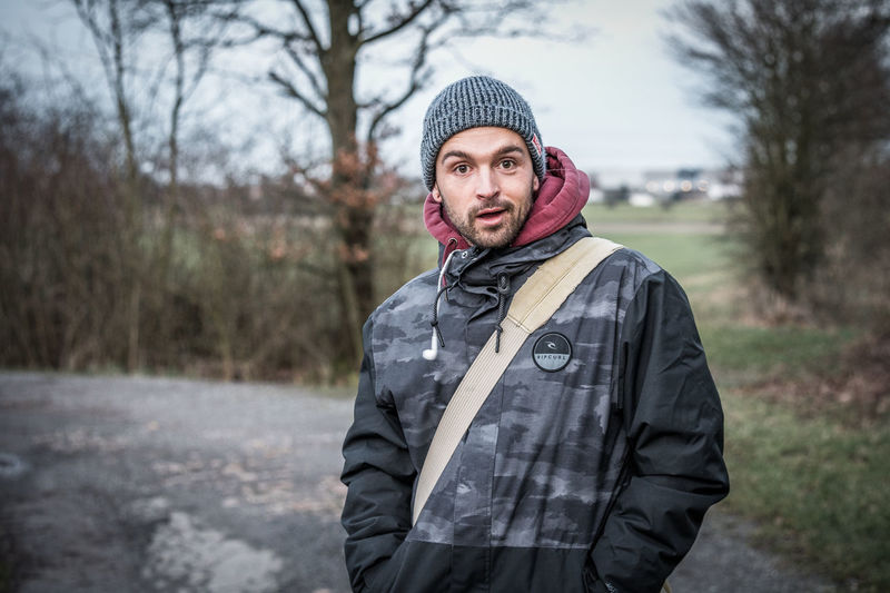 Portrait of young man standing against trees during winter