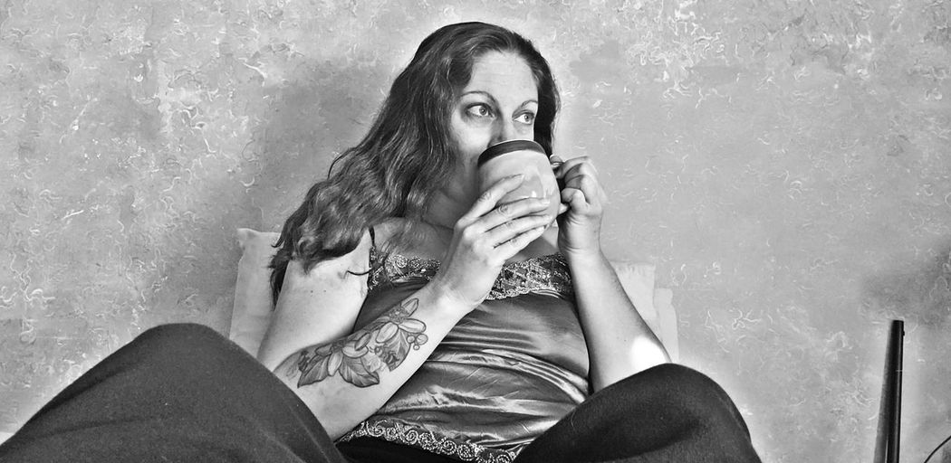 Low angle view of woman drinking coffee while sitting against wall