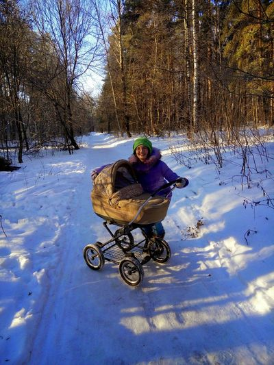 Woman with baby stroller on snow covered field against trees