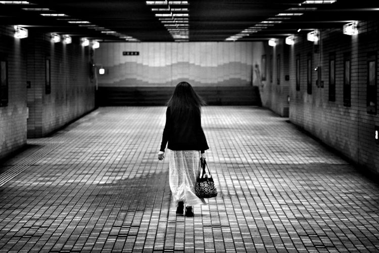 Rear View Of Woman With Bag Walking In Underground Walkway