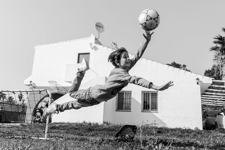 Boy playing soccer on field against house