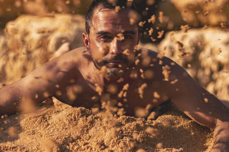 Portrait of young man in sand at beach