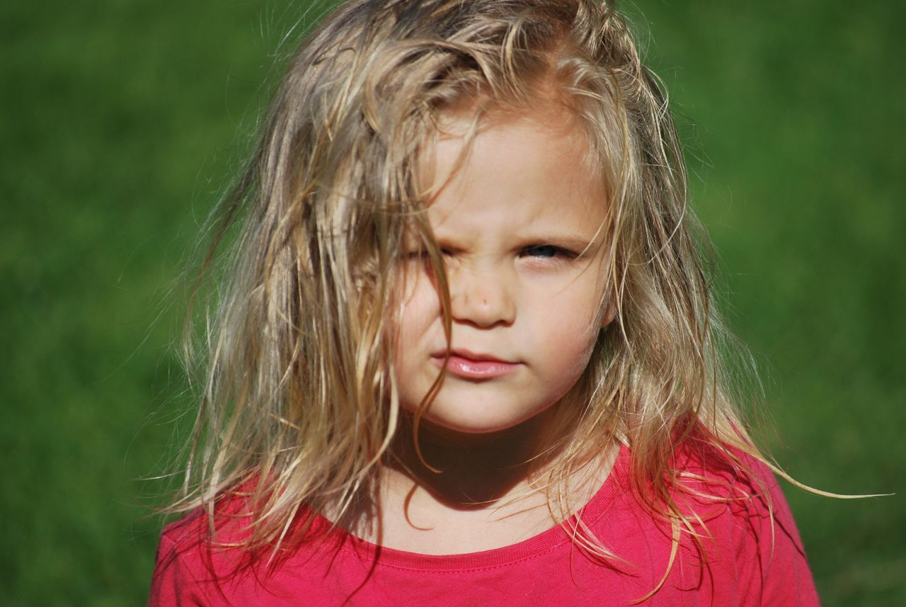 Close-Up Portrait Of Girl Standing On Grassy Field During Sunny Day