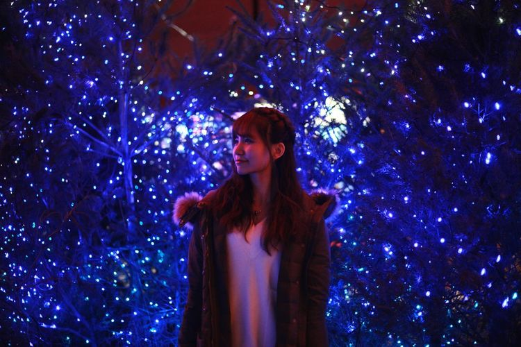 Woman with illuminated christmas tree against sky