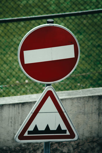 Road sign against fence