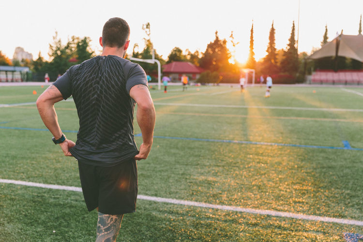 A man working out on a summer evening. Athlete Exercising Field Man Track And Field Active Fitness Healthy Lifestyle Lifestyles Outdoors Real People Sport Stretching Training Young Men