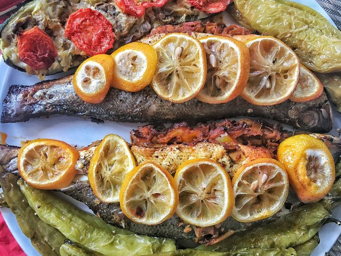 Close-up of fish with lemon and tomato slices in plate