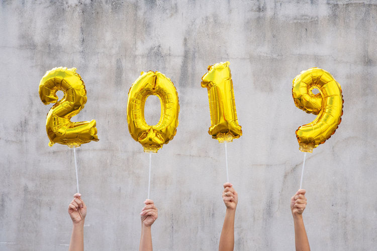 Hands holding golden 2019 balloons, new year concept New Year 2019 Golden Balloons Hands Holding Background White Background Christmas Number Human Hand Yellow Shiny Happy Color Human Body Part Wall - Building Feature Finger Hand Indoors  Body Part Communication Real People Human Finger