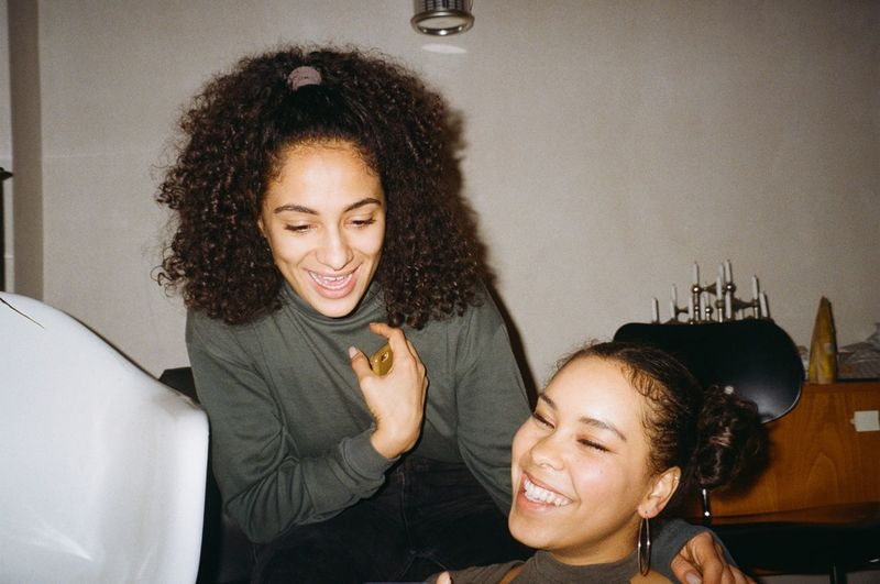 Smiling Happiness Indoors  Emotion Lifestyles Leisure Activity Young Women Portrait Real People Young Adult Curly Hair Cheerful Women Headshot Front View Casual Clothing Sitting Two People Teeth Toothy Smile Hairstyle Hair Positive Emotion NotYourCliche 35mm Film Moments Of Happiness