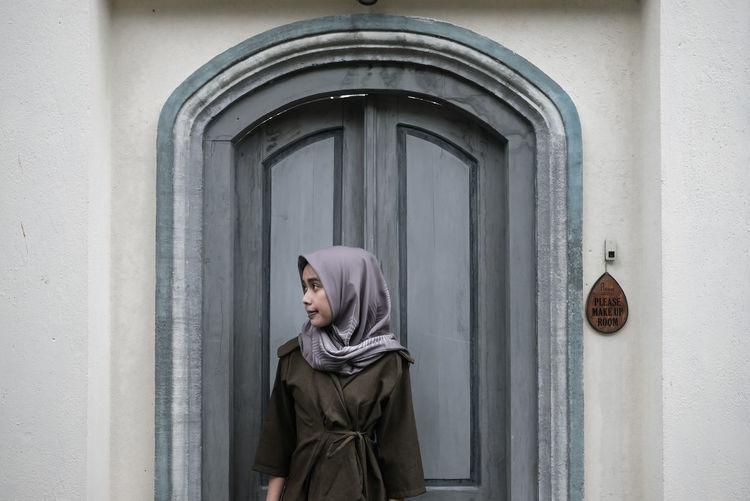 Portrait of woman with open door