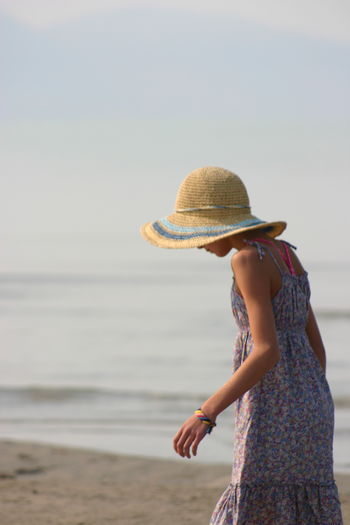 Rear view of girl wearing hat at beach against sky