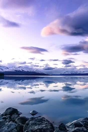 Scenic view of lake pukaki by snowcapped mountains against cloudy sky