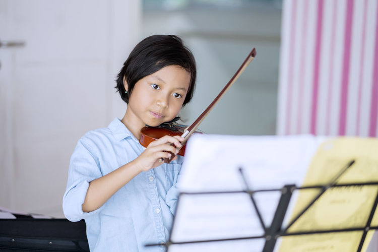 Cute Girl Playing Violin With Musical Note On Stand In Foreground