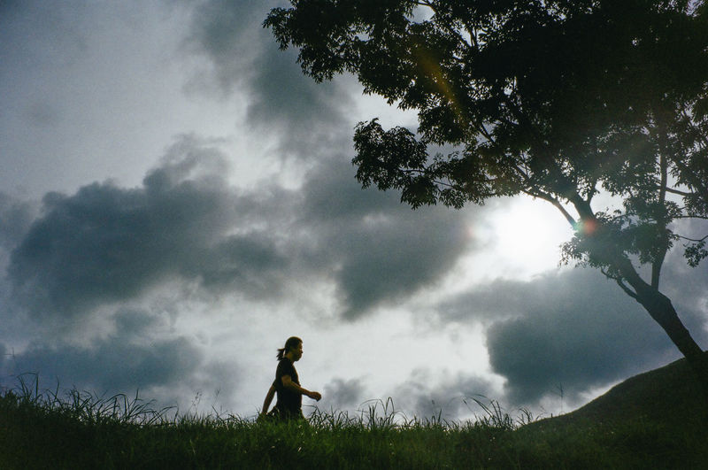 Low angle view of girl standing on field against sky