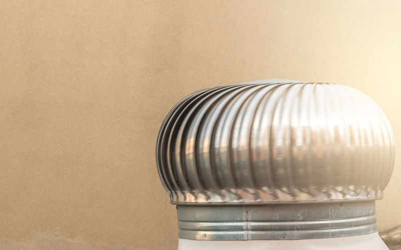 Close-up of aluminum exhaust against wall