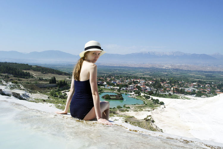 Portrait of young woman in swimwear sitting on mountain against blue sky during sunny day
