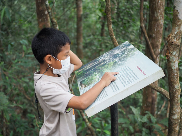 A boy standing and reading a tourist attraction in the national park