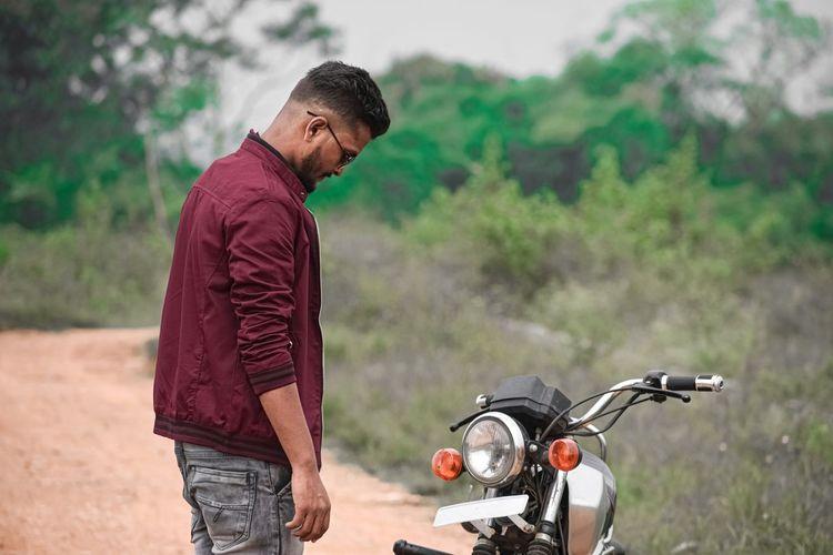 Young man looking at his bike.