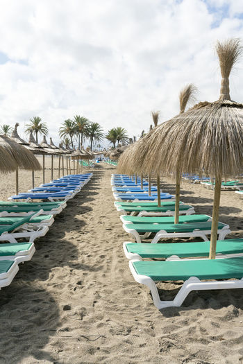 Beach Parasol Empty Beach Deserted Beach Deserted Straw Parasol Straw SPAIN Land Sand Sky Cloud - Sky Chair Lounge Chair Day Nature No People Seat In A Row Tree Roof Absence Palm Tree Umbrella Outdoors