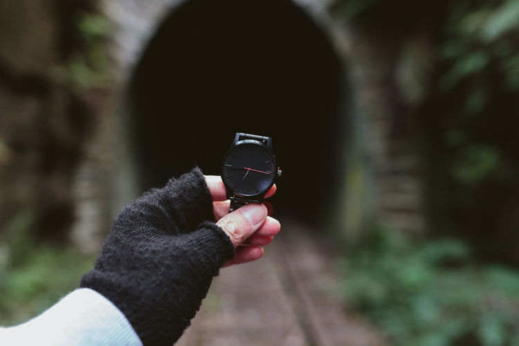 Cropped Image Of Person Holding Wristwatch By Tunnel