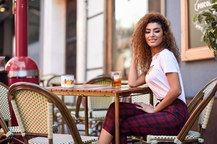 Side view portrait of young woman sitting at cafe table