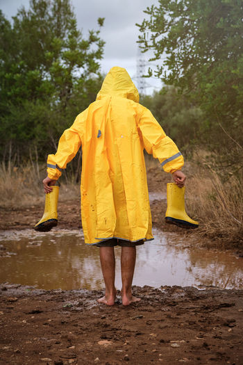 Rear view of person standing on wet road during rainy season
