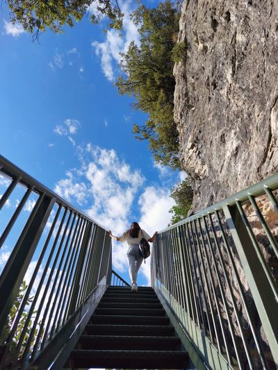 Low angle view of woman on footbridge