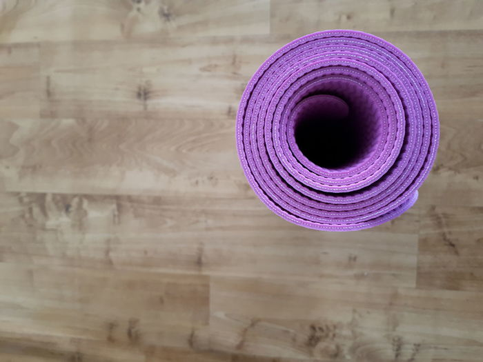 Directly Above Shot Of Purple Exercise Mat Rolled On Hardwood Floor