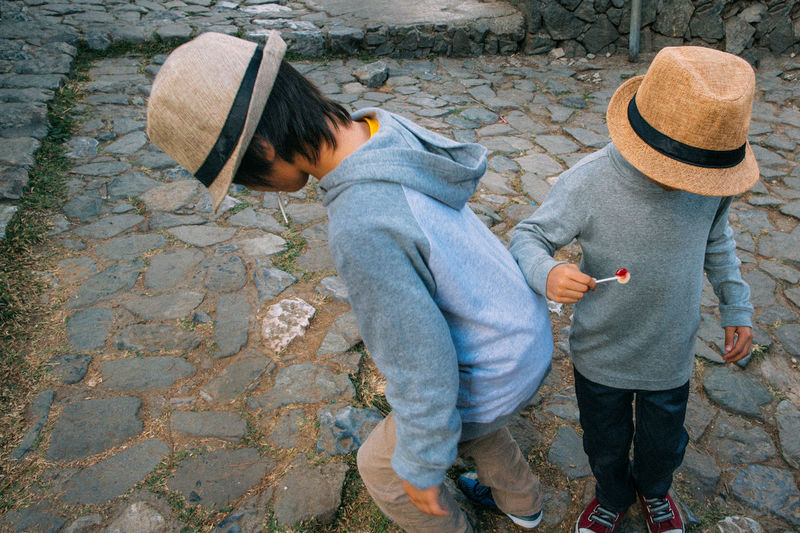 Two boys looking for something on the ground. Anonymous Asian  Boys Brothers Casual Clothing Hat Kids Leisure Activity Lifestyles Lollipop Long Sleeves Looking Down Looking For Something Play Playing Siblings