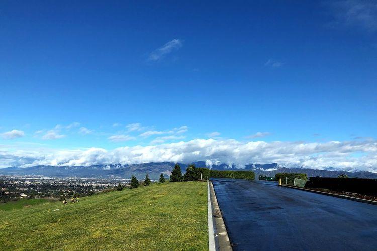 Road leading towards city against blue sky