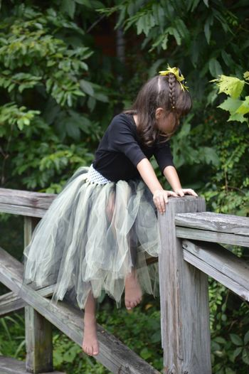 Girl Sitting On Wooden Railing At Park