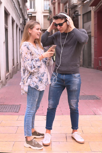 Full length of friends standing on footpath in city