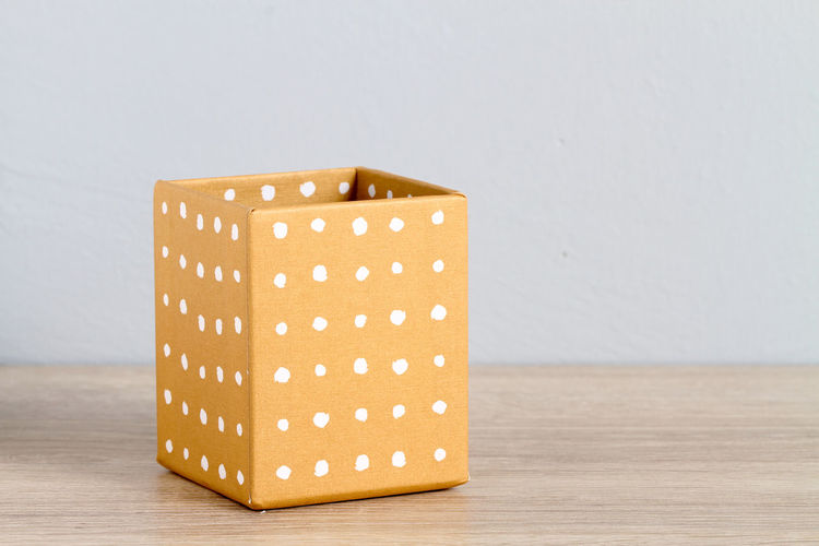 Close-up of box on table against white background
