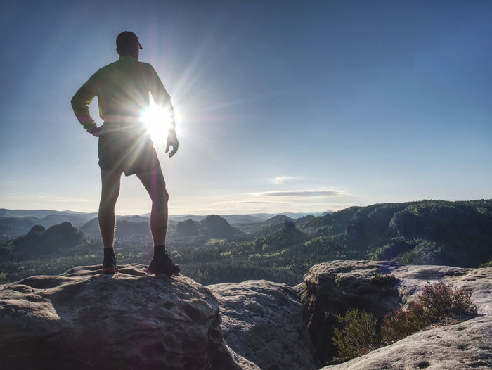 Trail runner athlete man. training in mountains in cold weather at sunset. amazing mountain peaks