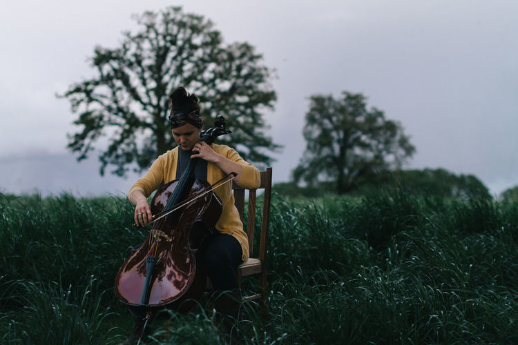 Woman playing cello at dusk in field Bow Grass Sitting Woman Beauty In Nature Casual Clothing Cello Day Dusk Field Full Length Grass Lifestyles Musician Nature One Person Outdoors People Real People Sitting Sky String Instrument Tree Young Adult Young Women