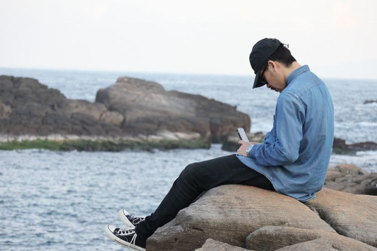 Side View Of Young Man Using Phone While Sitting On Rock At Beach