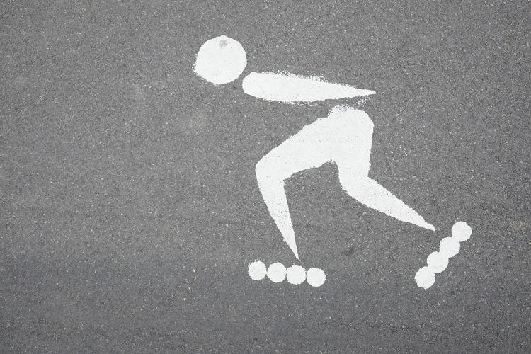 symbol of roller skating on the asphalt Sign Road Human Representation Communication Day Outdoors Road Marking Symbol Roller Skating Man Sport