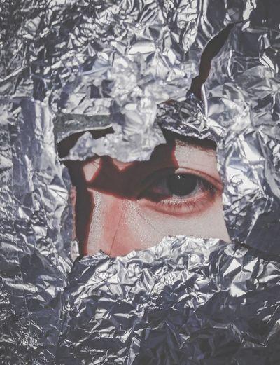 Close-up portrait of woman seen through foil paper
