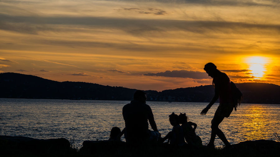 Silhouette family against river during sunset