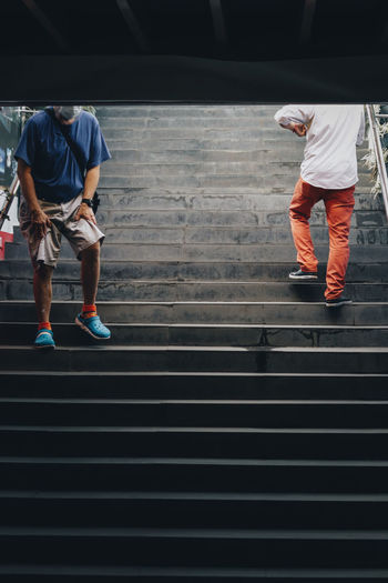 Rear view of men walking on staircase