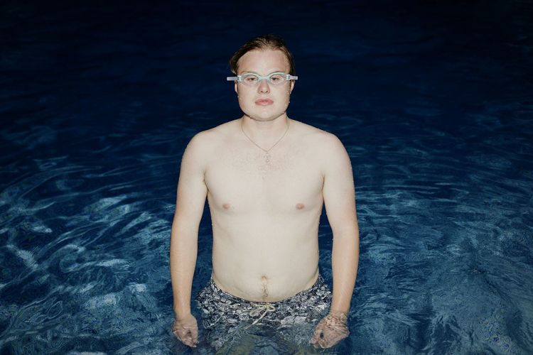 Portrait of shirtless man in pool at night