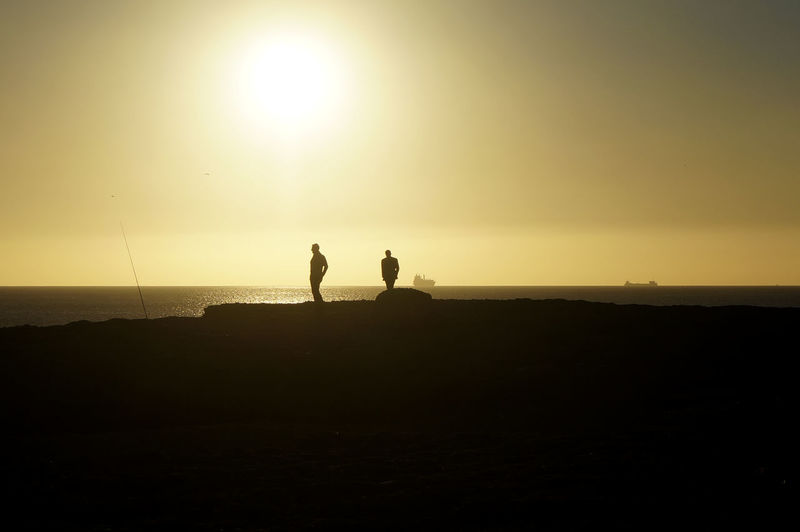 Two Silhouette People Standing On Calm Beach