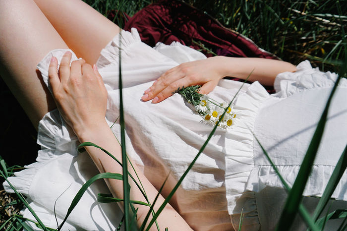 MIDSECTION OF WOMAN AND WHITE FLOWERING PLANTS
