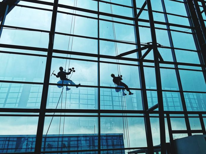 Low angle view of man working on glass window