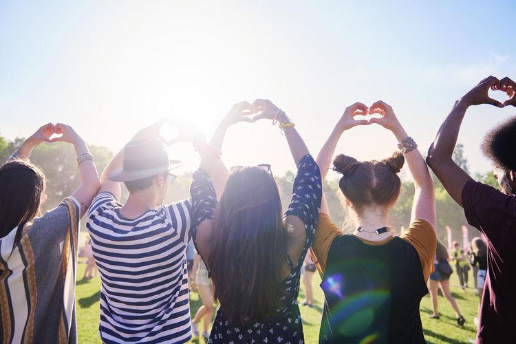 Rear view of friends making heart shape at music festival