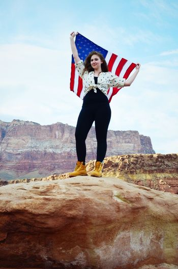 Low Angle View Of Young Woman Holding American Flag While Standing In Rocks At Grand Canyon