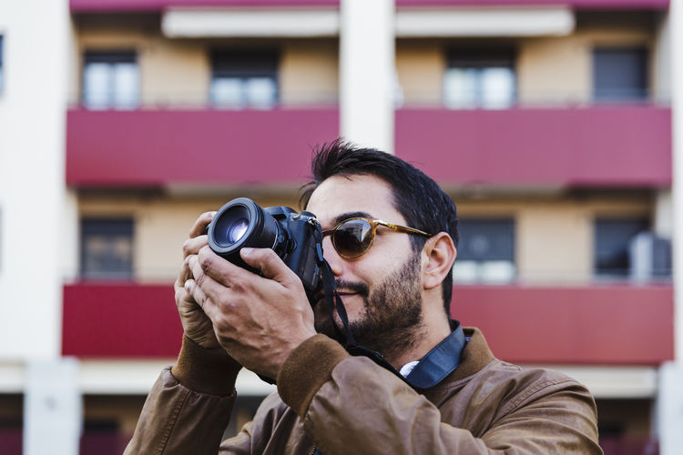Man wearing sunglasses photographing with camera against building
